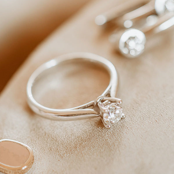 A beautiful silver ring and earrings with a diamond on a beige background. decoration. close-up